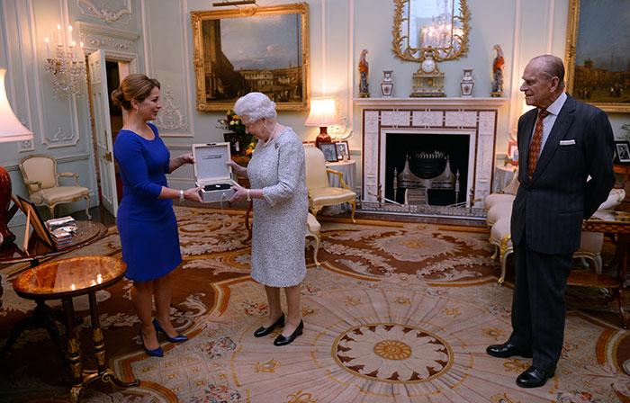 Queen Elizabeth II is presented with the Federation Equestre Internationale (FEI) lifetime achievement awards Haya of Jordan (left), as the Duke of Edinburgh